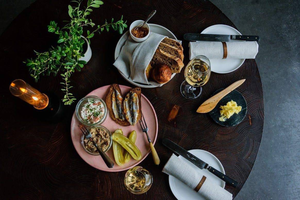From above, a plate of sardines, pickles and spread with bread, a bread basket, and other plates on a dark wood table