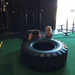 Jennifer Taylor explains how the tire flip works to her 5-year-old daughter, Ashley, during the family fitness class at Pure Workout Sunday morning. The class was one of two that raised money for the family of Memorez and Jase Rackley, who were killed in a shooting last Tuesday.