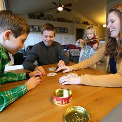 Luke Widdison, Isaac Widdison and Emily Widdison play a game as Penny Widdison practices vioin at their home in Saratoga Springs, Utah, Friday, Jan. 8, 2016.