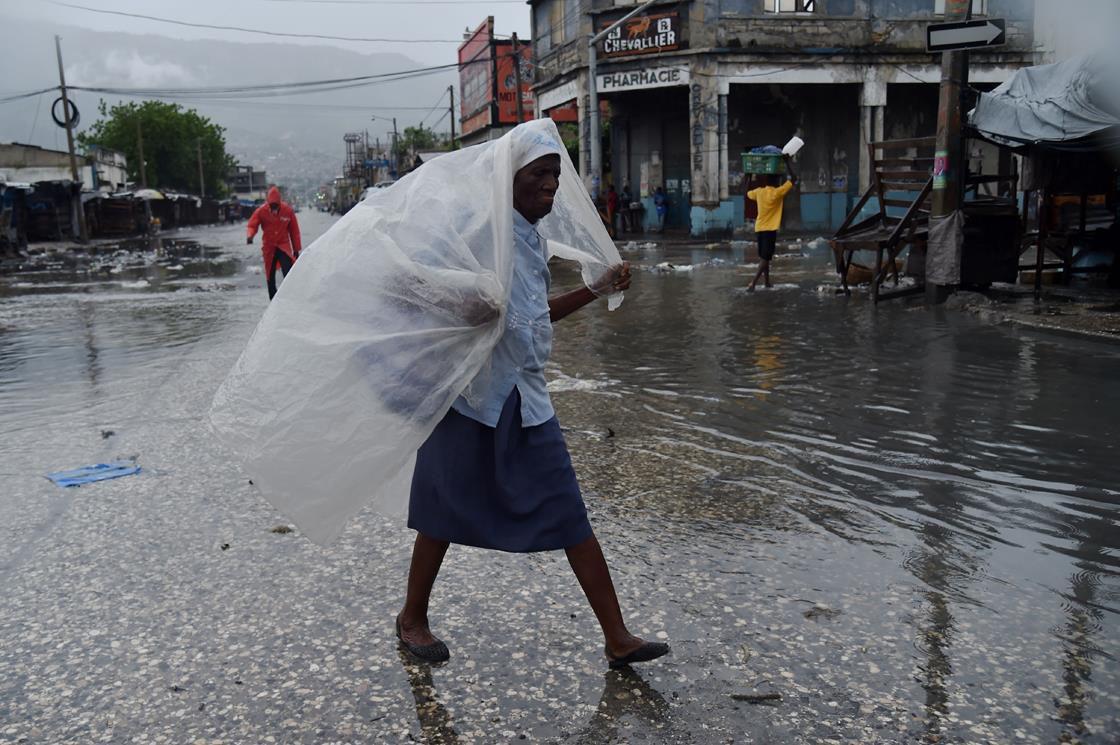 Haitian woman walking down flooded street