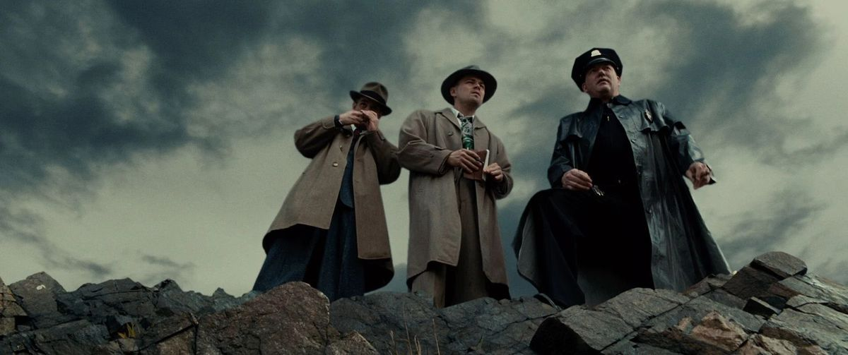 Three detectives stare out over a cliffside in Shutter island