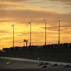A group of cars go into turn one as the sun sets during the NASCAR Nationwide Series auto race at Atlanta Motor Speedway, Saturday, Sept. 1, 2012, in Hampton, Ga.