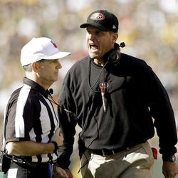 San Francisco 49ers head coach Jim Harbaugh argues a call with referee David White during the first half of an NFL football game against the Green Bay Packers Sunday, Sept. 9, 2012, in Green Bay, Wis.