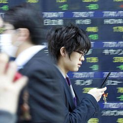 People walk by an electronic stock board of a securities firm in Tokyo as Tokyo's Nikkei 225 index lost 142.19 points, or 1.47 percent at 9,546.26 Monday, April 9, 2012. Asian stock markets declined Monday after U.S. hiring slowed in March, raising doubts about the durability of the recovery in the world's No. 1 economy.
