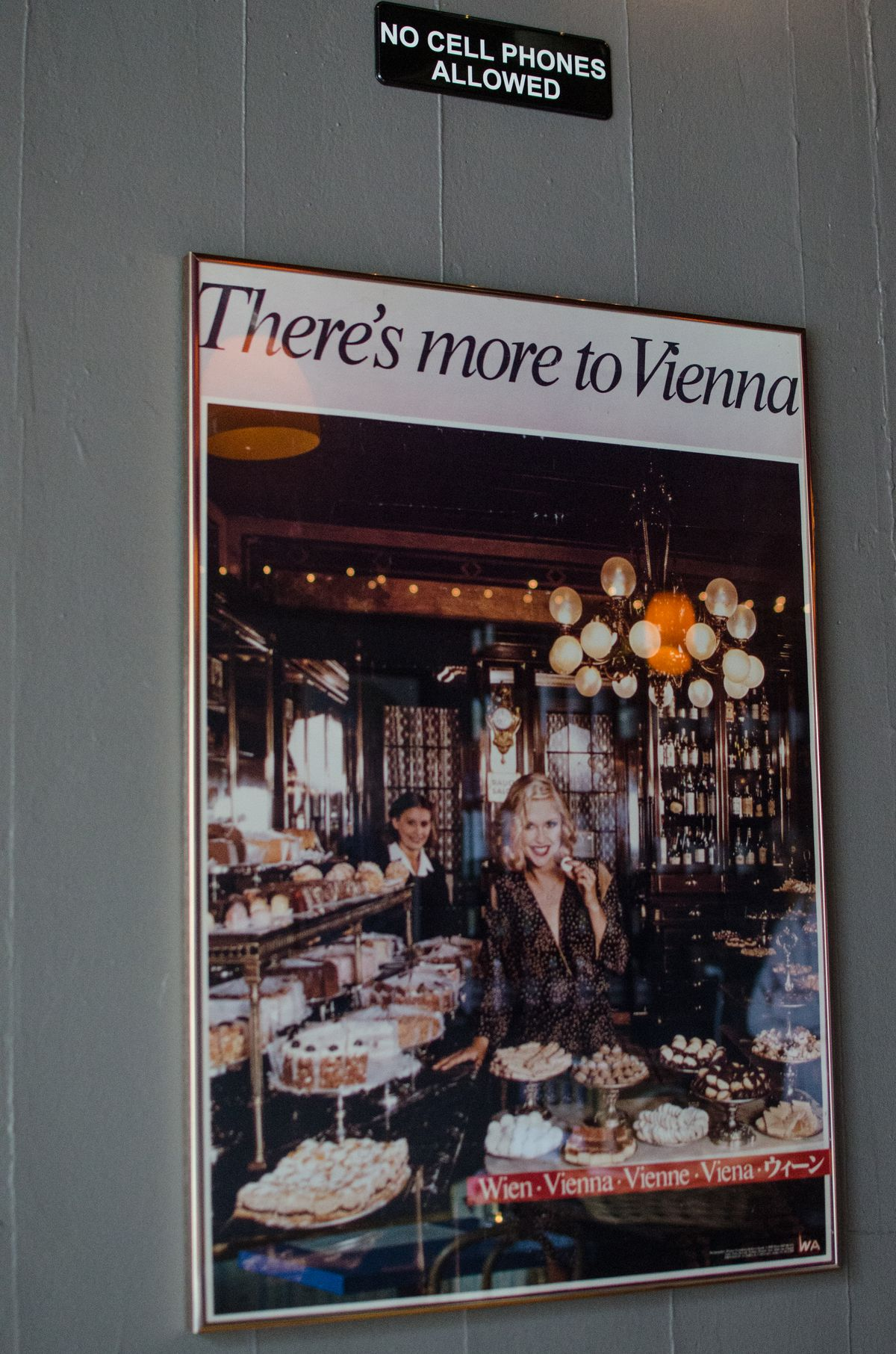 """On a gray wall, there's a small black sign with white lettering that says """"No Cell Phones Allowed."""" Under it is a vintage poster that says """"there's more to Vienna,"""" featuring a blonde woman at a dessert buffet."""