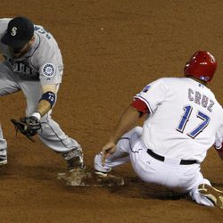 Seattle Mariners second baseman Dustin Ackley (13) tags out Nelson Cruz (17) who was trying to get back to second after David Murphy flied out to short for a double play in the sixth inning of a baseball game Friday, Sept. 14, 2012, in Arlington, Texas.