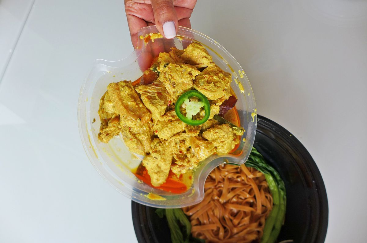 A hand holds a clear plastic tray of chicken poised over a bowl of noodles.