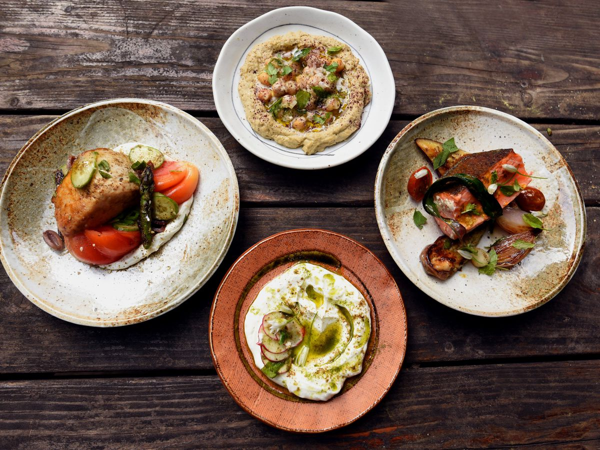 A spread of four dishes including a hummus plate laid out over a dark wood table.