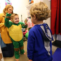 Emily Widdison helps Max Widdison dress up as a Ninja Turtle and Simon Widdison dress up as Superman at their home in Saratoga Springs, Utah, Friday, Jan. 8, 2016.