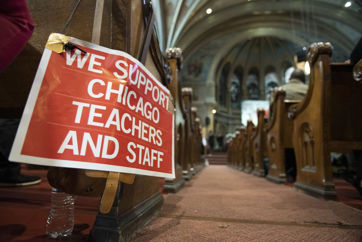 A sign for the Chicago Teachers Union sits next to an attendee at a solidarity rally for the Chicago Teachers Union on Sunday at New Mt. Pilgrim MB Church in West Garfield Park.