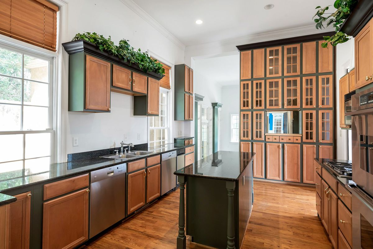 A huge kitchen with wooden cabinets and a few columns.