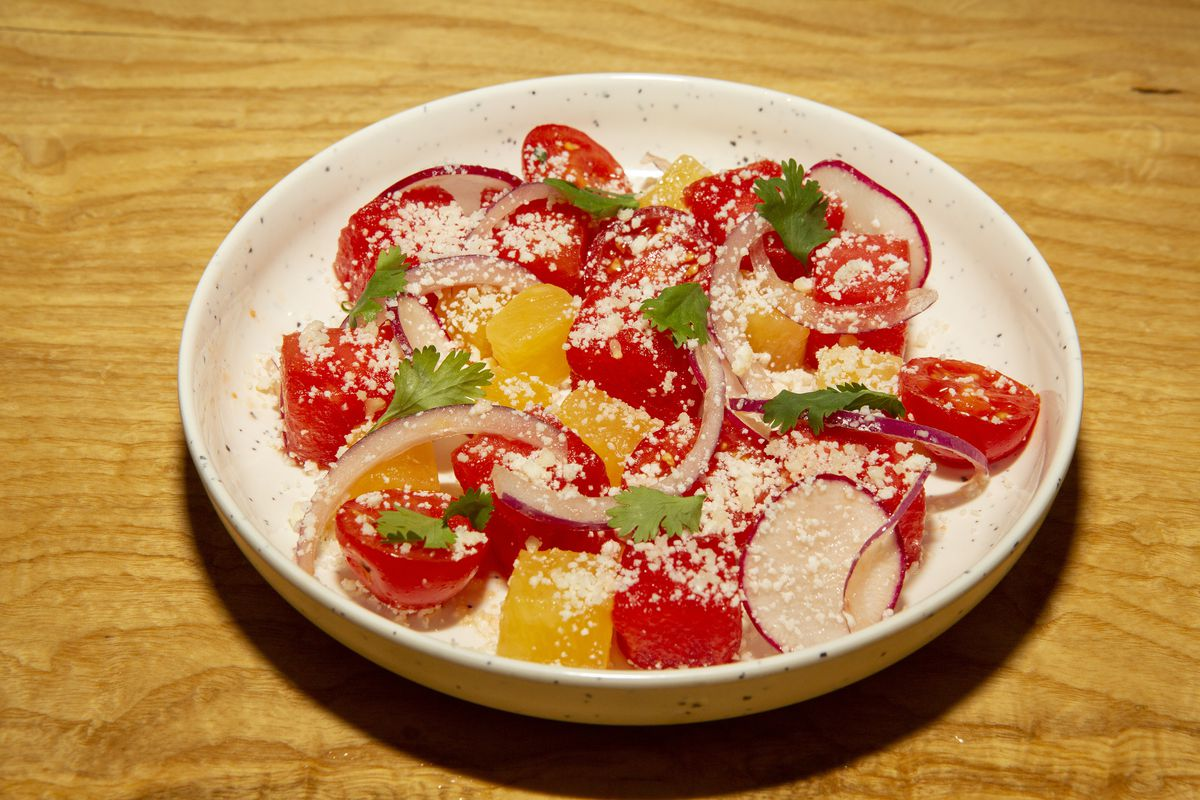 A white bowl holds bright red cubes of watermelon dusted with white cotija cheese