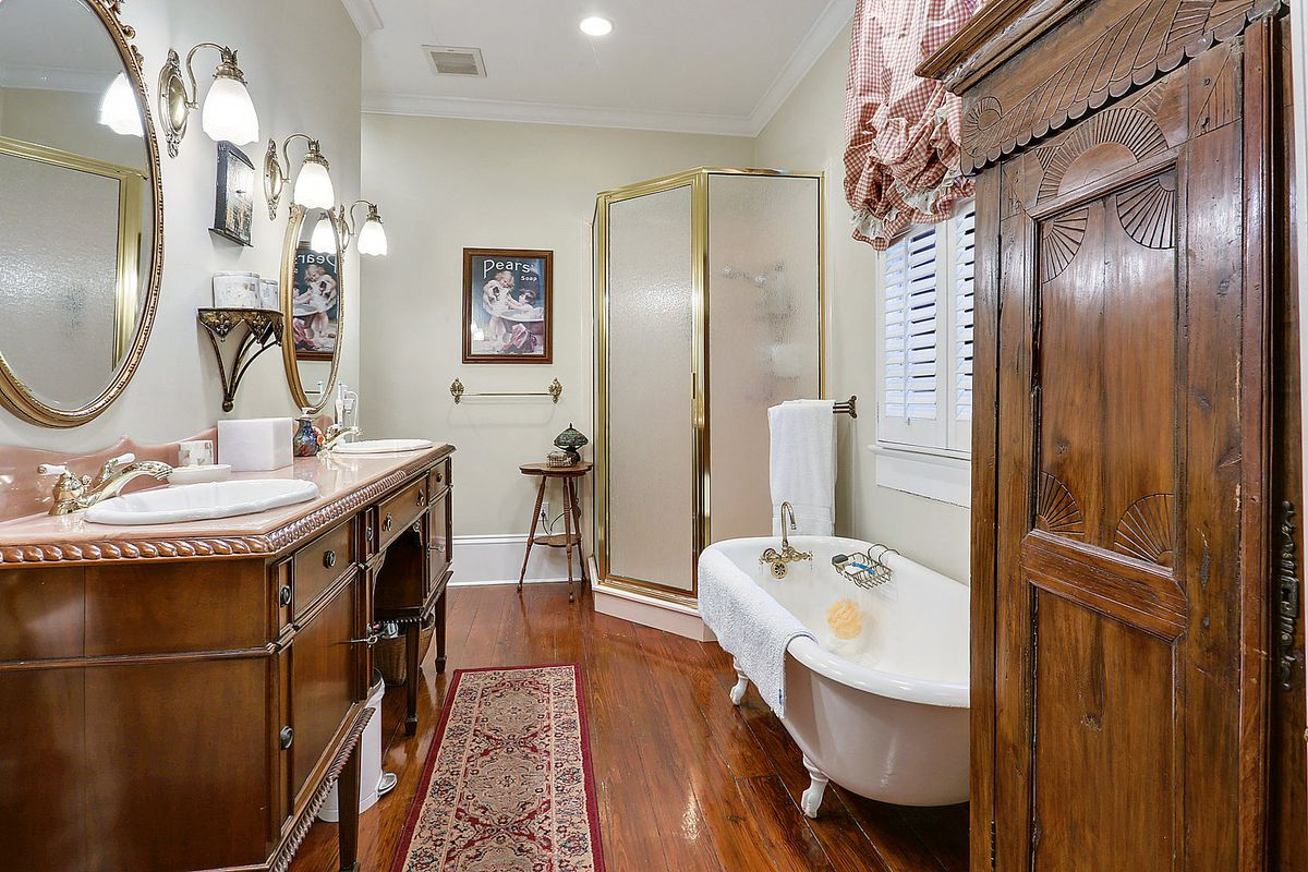 Bathroom with clawfood tub and armoire, plus double sinks
