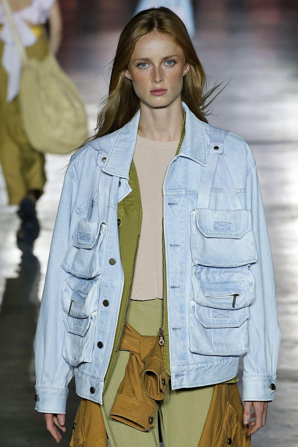 A model wears a blue denim jacket with three pockets on each breast.