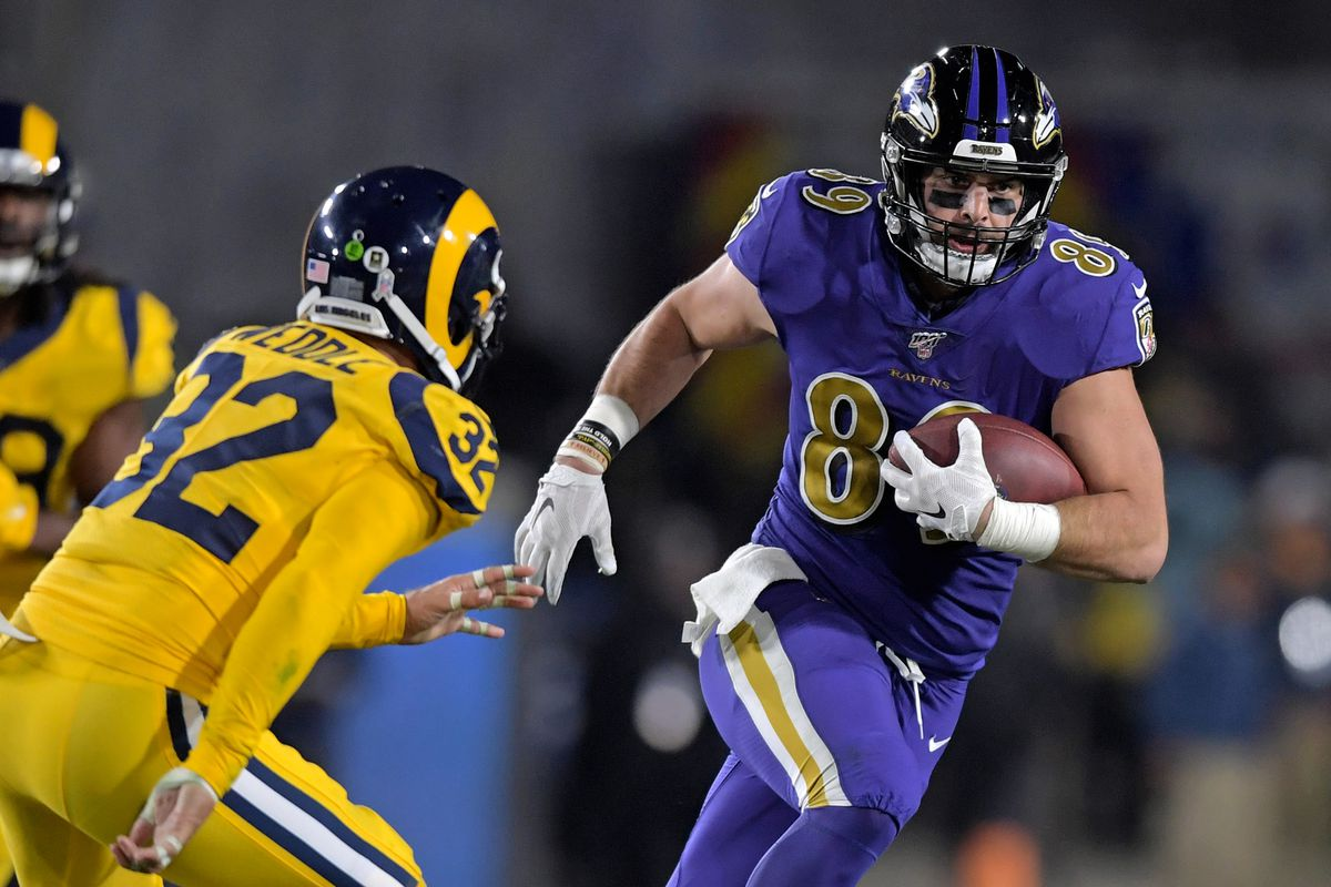 Baltimore Ravens tight end Mark Andrews carries the ball past Los Angeles Rams free safety Eric Weddle during the second half at Los Angeles Memorial Coliseum.