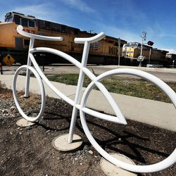 A train passes by a ghost bike memorial in honor of Douglas Crow in Provo, Wednesday, May 20, 2015. Crow was an avid cyclist who died Feb. 13, 2013.