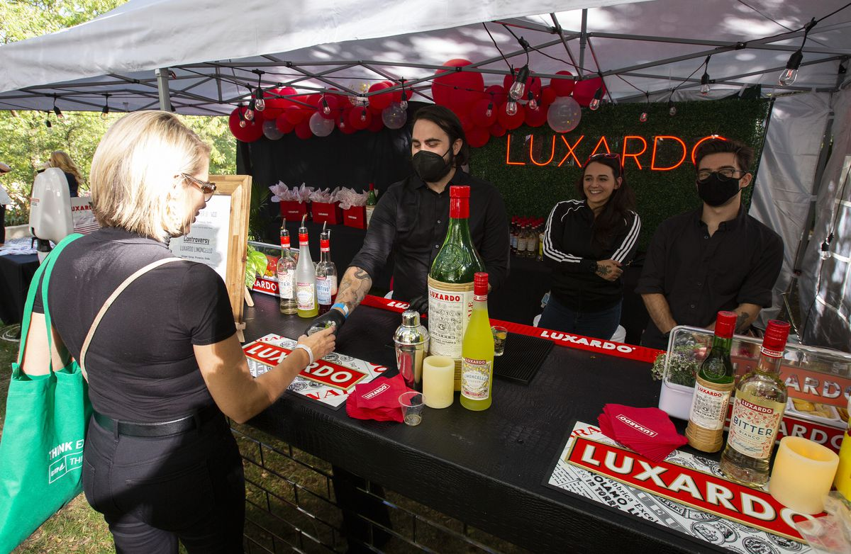 A masked bartender inside a red tent hands a drink to a customer
