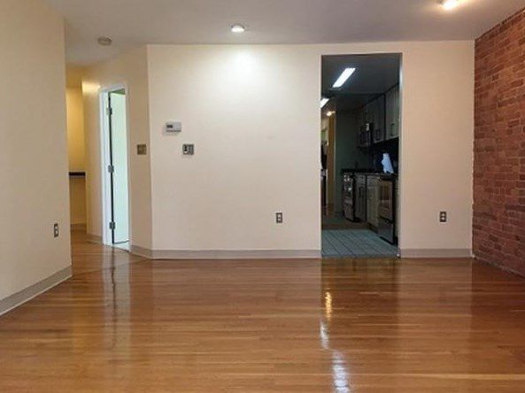 An empty living room leading to a small kitchen.