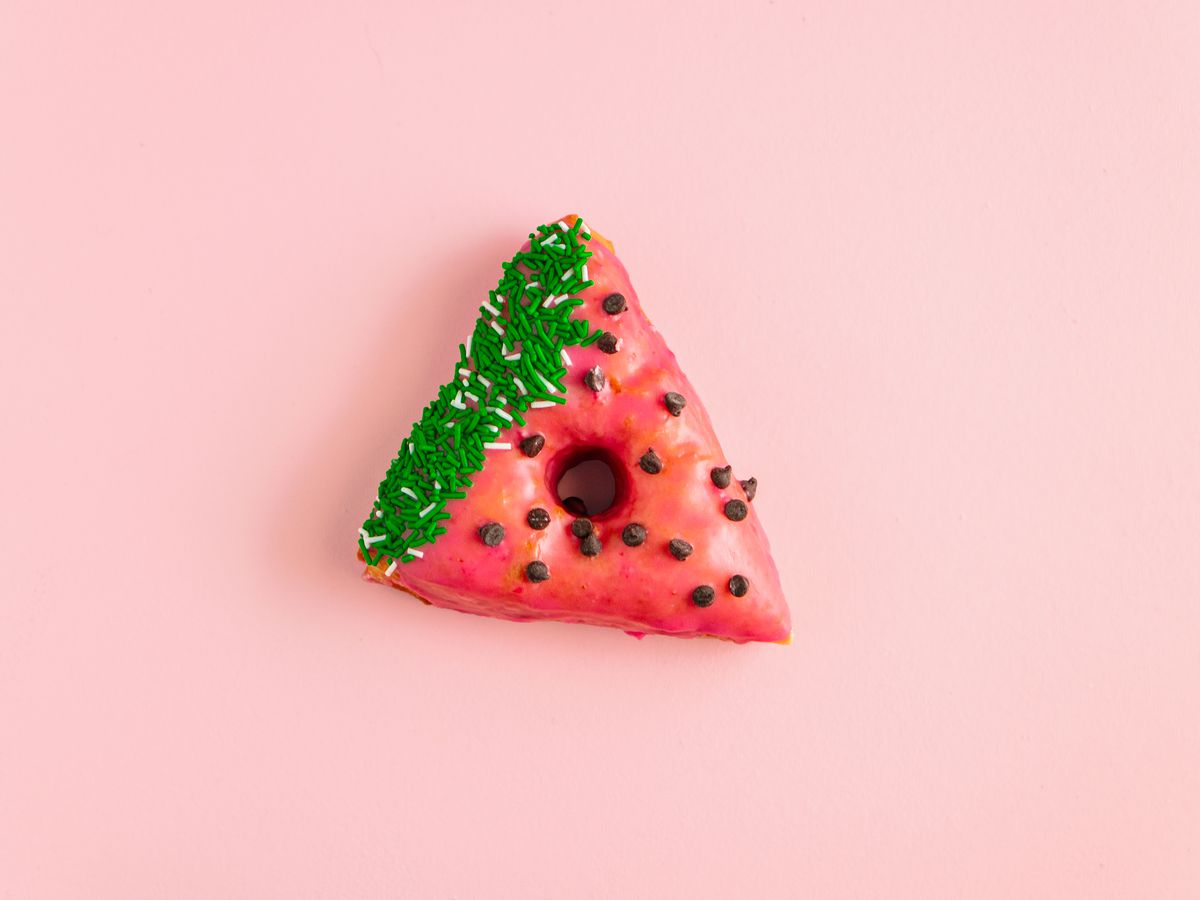 A triangular doughnut decorated like a watermelon sits on a pale pink background