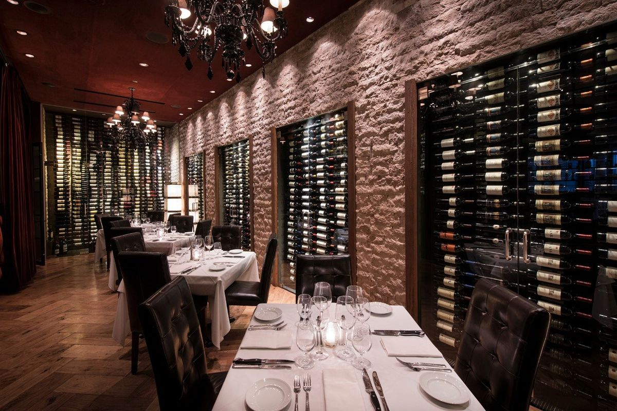 An empty steakhouse with brick walls and lots of wine