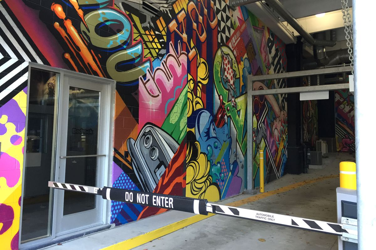 Dan Gilbert's massive new downtown parking garage is covered with colorful murals — an experience you wouldn't get in the suburbs, he says.