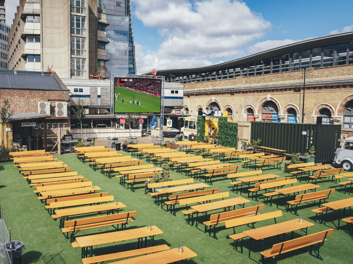 Wooden benches and tables on astroturf at Vinegar Yard in London, with a huge screen for watching football