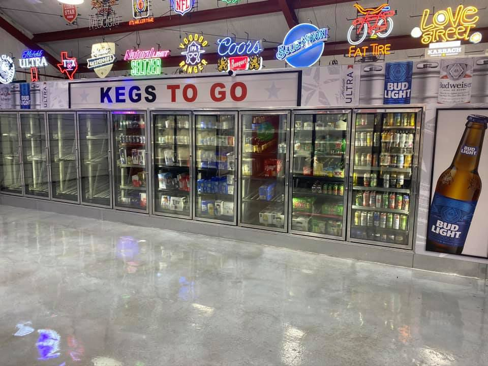 """A very large fridge with """"Kegs to Go"""" in front of concrete floors"""