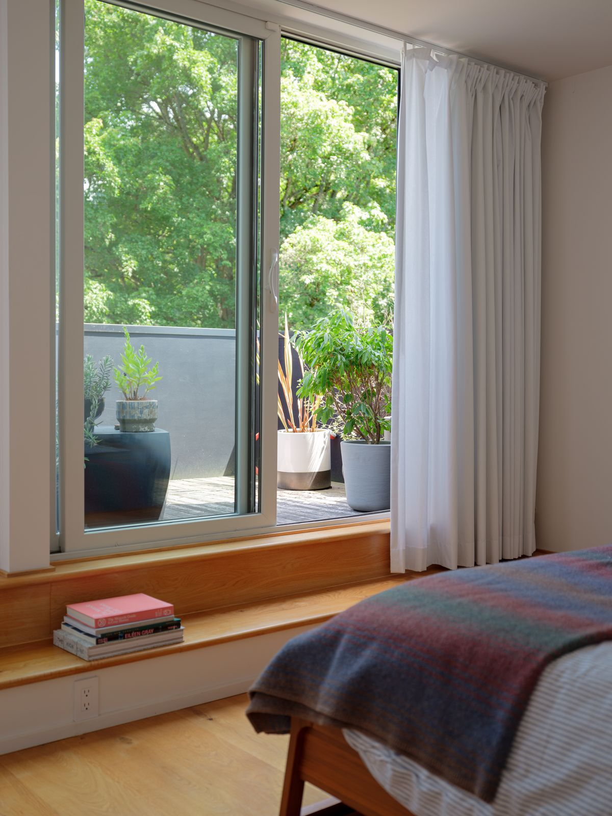 A bedroom area with a bed that has a colorful patterned blanket. There are glass doors with a view overlooking a patio with multiple potted plants. There is a step that has a pile of books stacked on it.