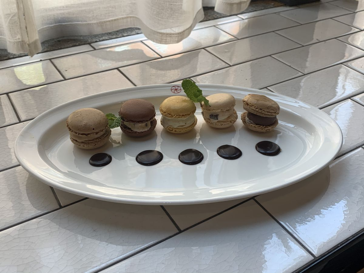 Ice cream and macaron sliders in several flavors line a white plate and sit on a white subway tile surface