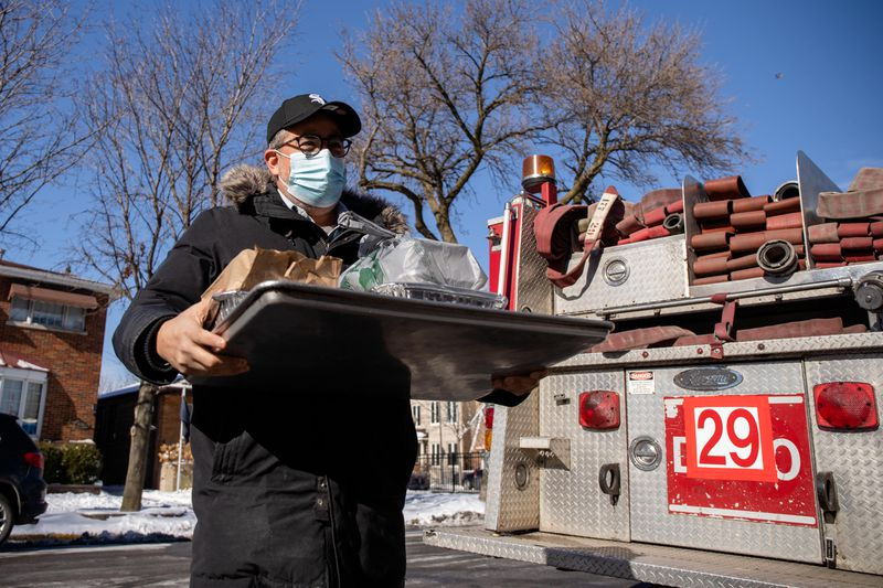 Omar Solis, owner of Nana restaurant group, delivers food to firefighters Thursday at Engine 29 in Bridgeport. White Sox pitcher Liam Hendriks and his wife Kristi donated food from local restaurants to the Chicago Fire Department firefighters.
