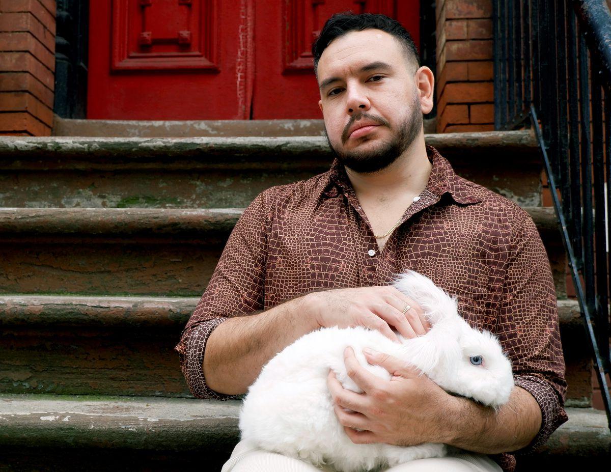 Author John Paul Brammer holding a bunny on a stoop.