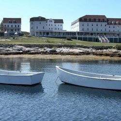In this photo taken Friday, Sept. 14, 2012, dories float in the bay in front of the historic Star Island Family Retreat and Conference Center, and the Oceanic Hotel, far right, at the Isle of Shoals in Rye, N.H. The hotel, 10 miles off the coast of New Hampshire, wants to establish itself as an environmental leader. The island is essentially a self-contained system, and it is an ideal spot to showcase energy innovations and could be become a model for other communities.