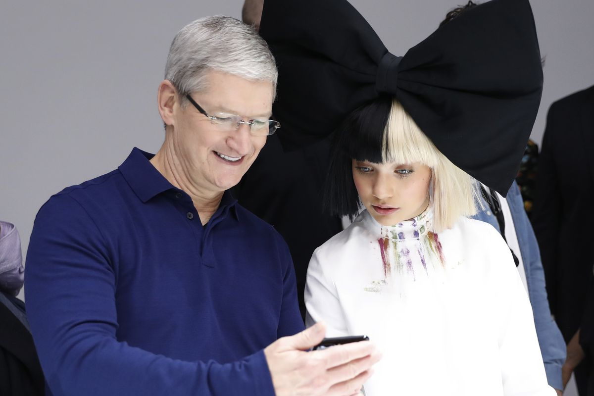 Apple CEO Tim Cook (L) and dancer Maddie Ziegler are seen in the product demonstration area during a launch event on September 7, 2016 in San Francisco, California. Apple Inc. unveiled the latest iterations of its smart phone, the iPhone 7 and 7 Plus, the
