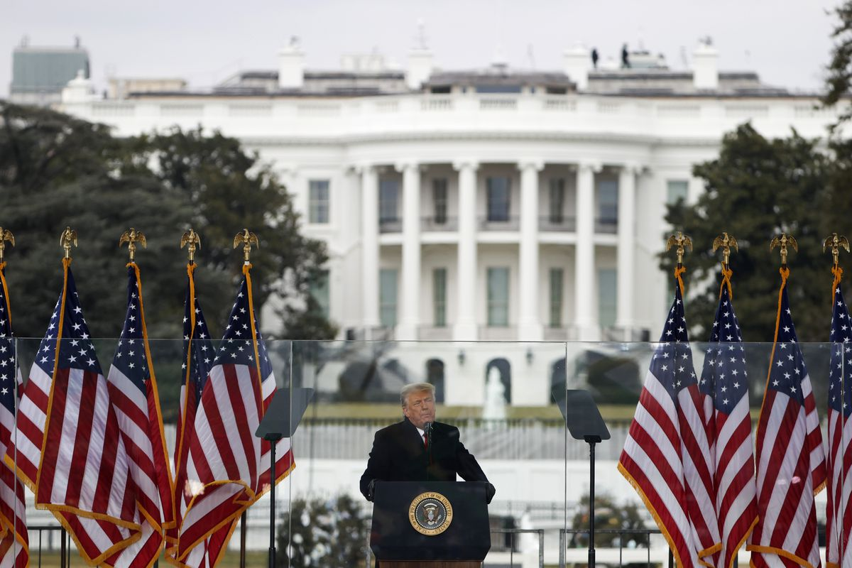 Donald Trump speaking in front of the White House between many American flags.