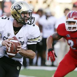 Colorado's Connor Wood is flushed out of the pocket by Fresno State's Donavon Lewis in the first quarter of an NCAA college football game in Fresno, Calif., Saturday, Sept. 15, 2012.