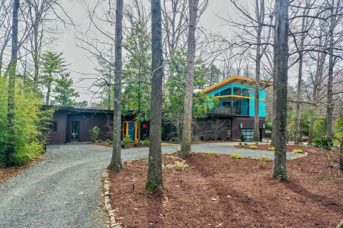 A ranch home with a two-story second addition sits behind trees and a driveway.