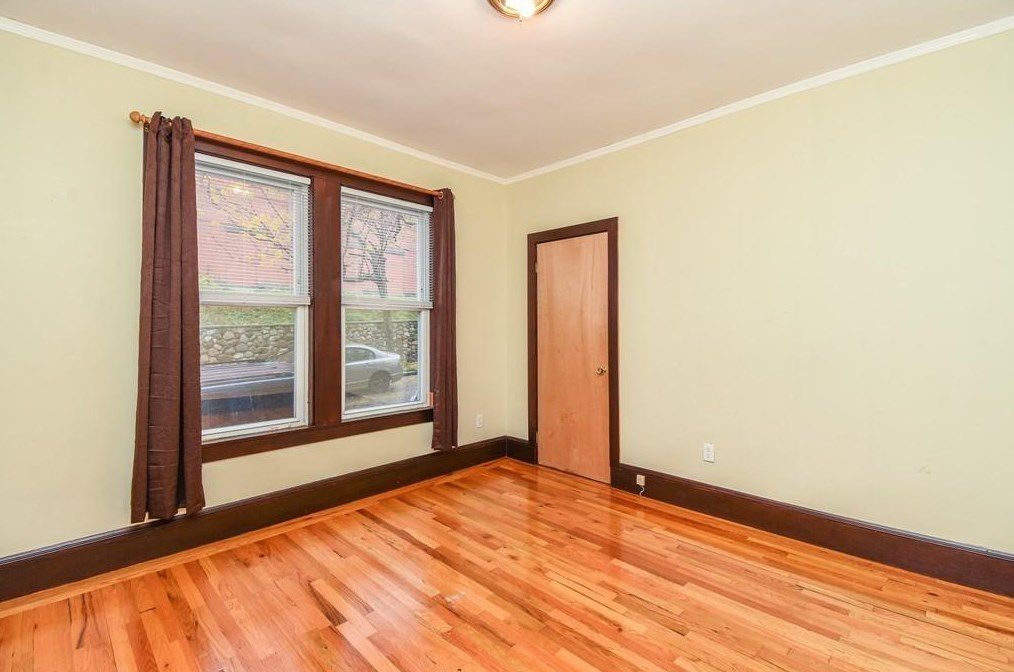 An empty room with two windows and a closed closet.