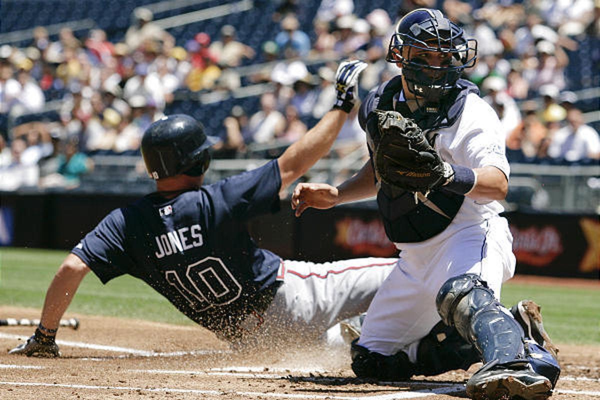 Atlanta Braves' Chipper Jones scores as San Diego Padres catcher Eliezer Alfonzo tries to field an off-line throw Wednesday.