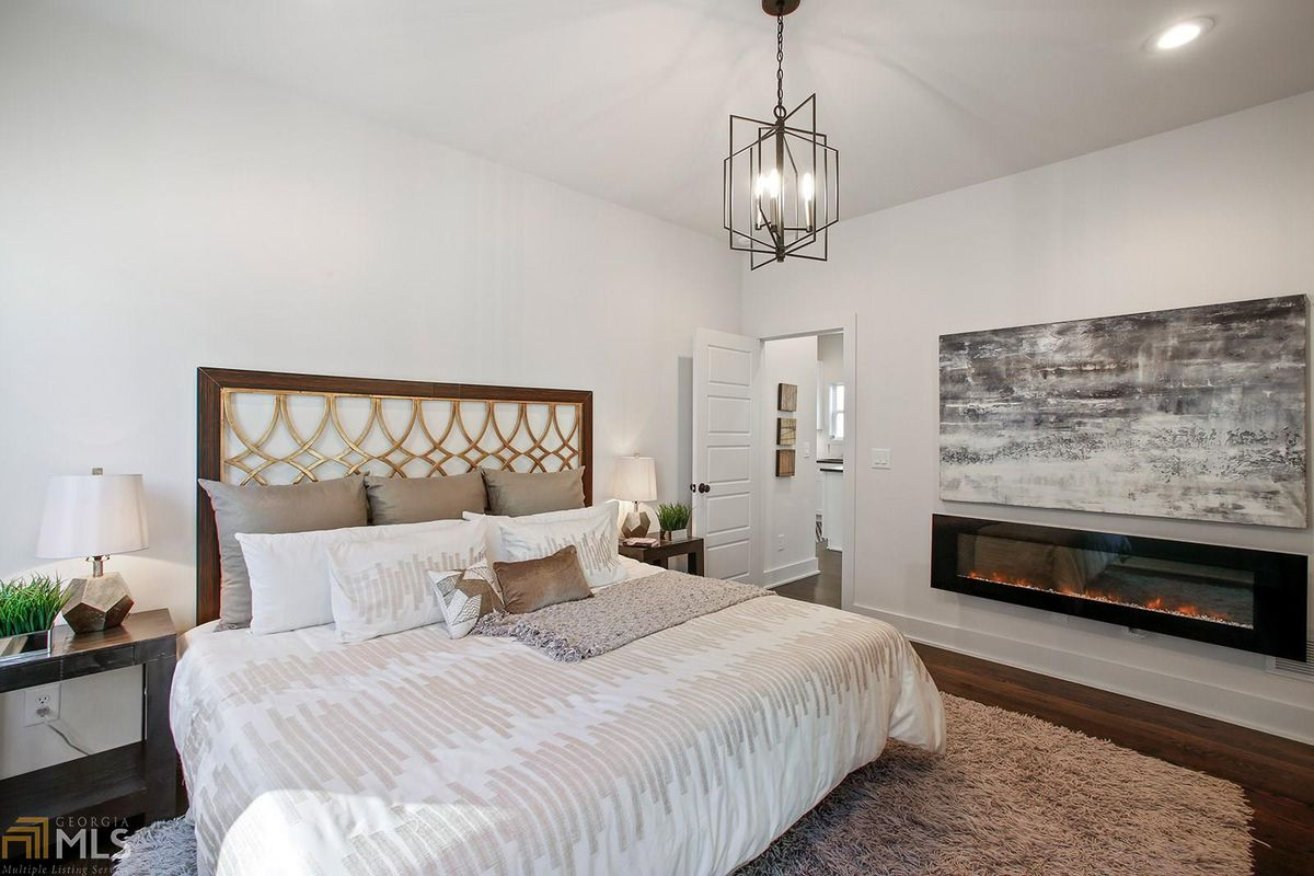Bedroom with king bed, nightstands with lamps, an area rug, and a faux fireplace.
