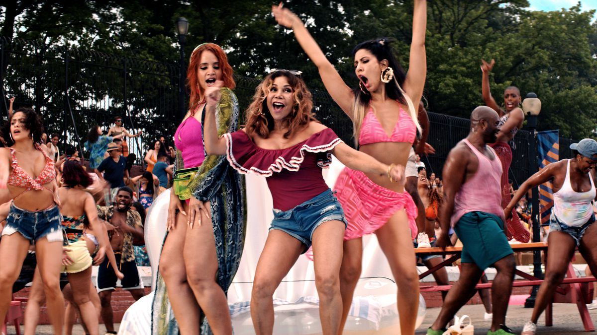 three girls dance in bathing suits and shorts during a summer dance party in In the Heights