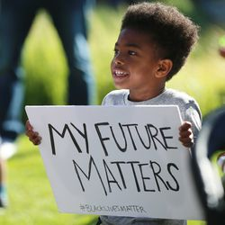Julius Rowe Jr. holds a sign as he joins his family and several hundred other demonstrators who gathered to march for Black Lives Matter at Daybreak in South Jordan on Wednesday, June 17, 2020.