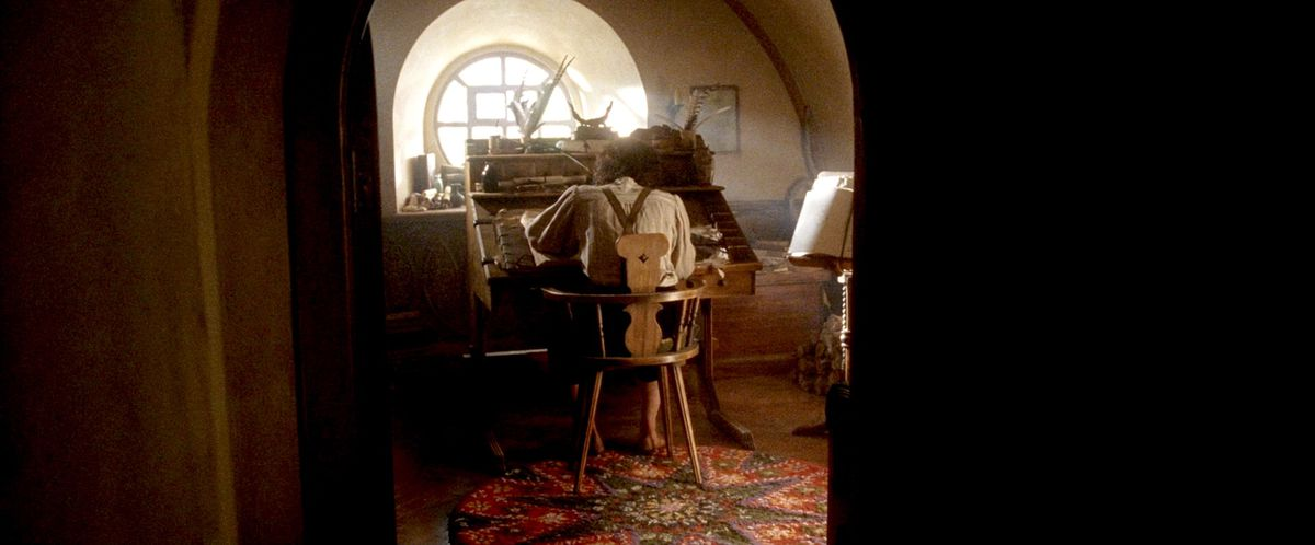 Frodo, back to camera, writes the Lord of the Rings at Bilbo's sunlit desk in Return of the King