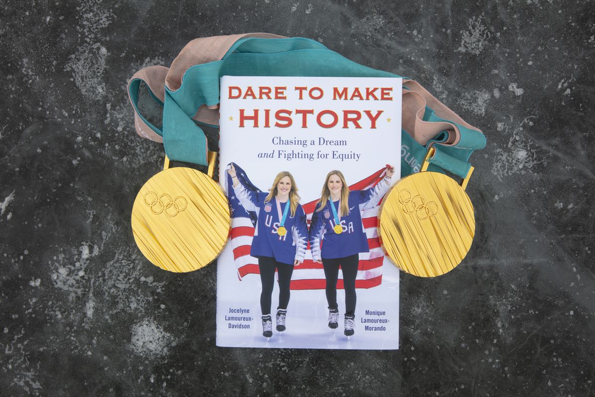 """The book """"Dare to Make History"""", featuring Jocelyne Lamoureux-Davidson and Monique Lamoureux-Morando on the cover, rests on a black ice surface in between their 2018 Olympic gold medals."""