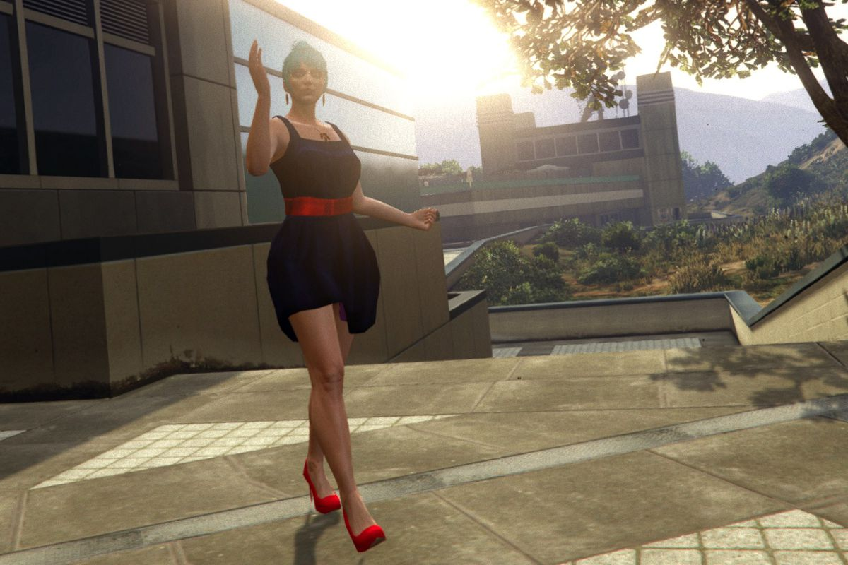 Grand Theft Auto Online - a blue haired woman in a dark blue dress walks and waves. She looks professional, and she is entering a large stage venue as the sun is in the sky behind her.