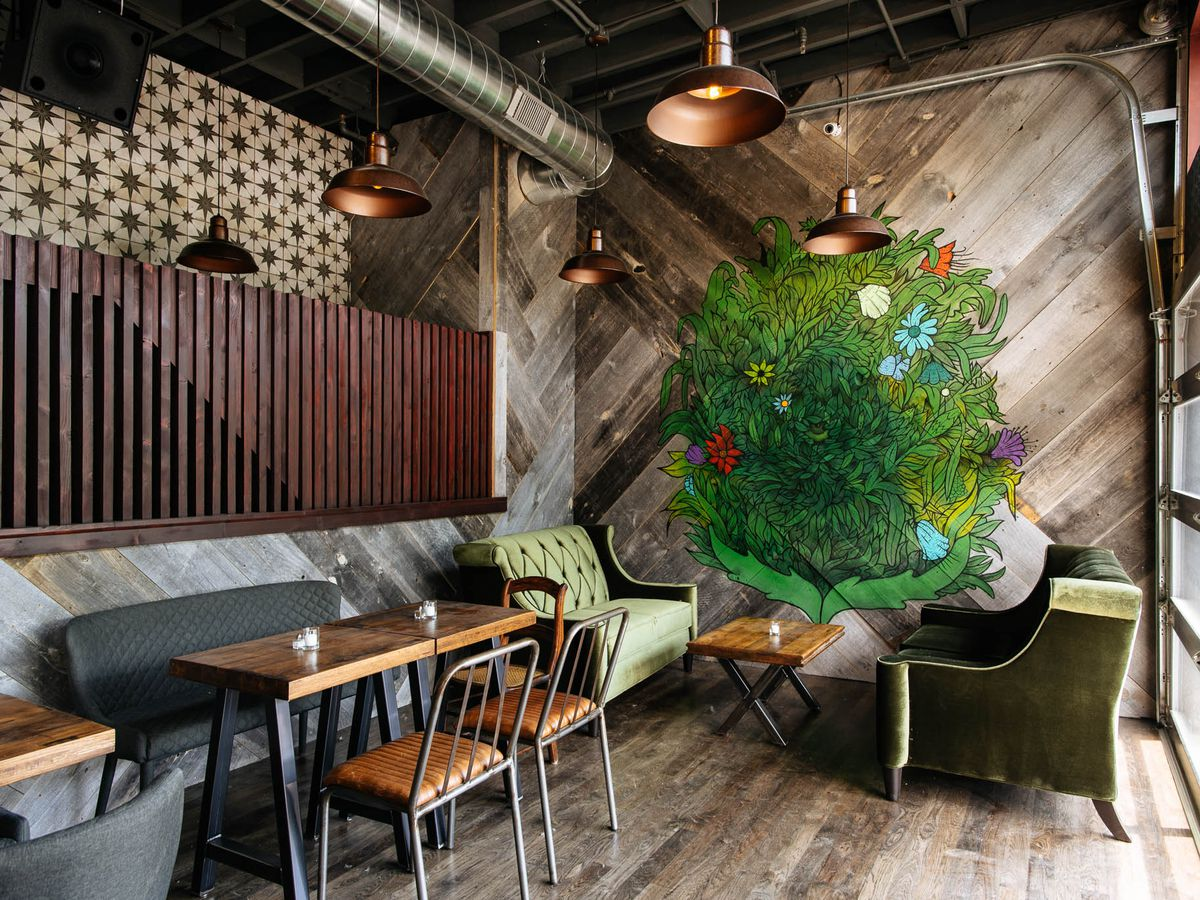 Barroom with sofas and a mural of foliage