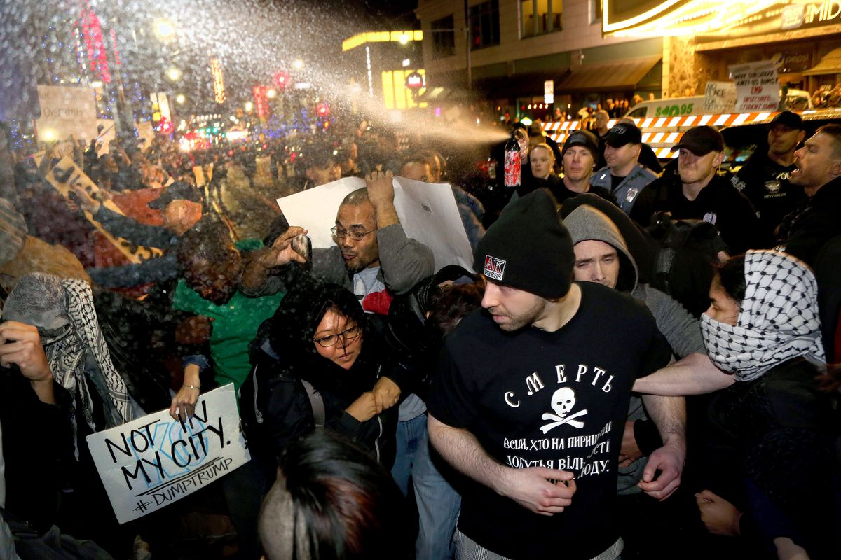 Police pepper-spray a group of protesters at a Donald Trump rally in Kansas City.