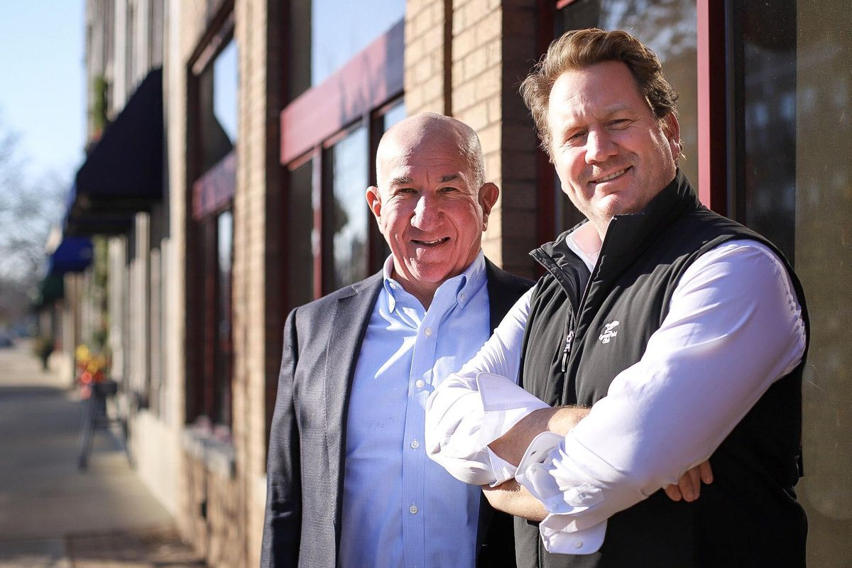 Two white men pose beside a brick building.