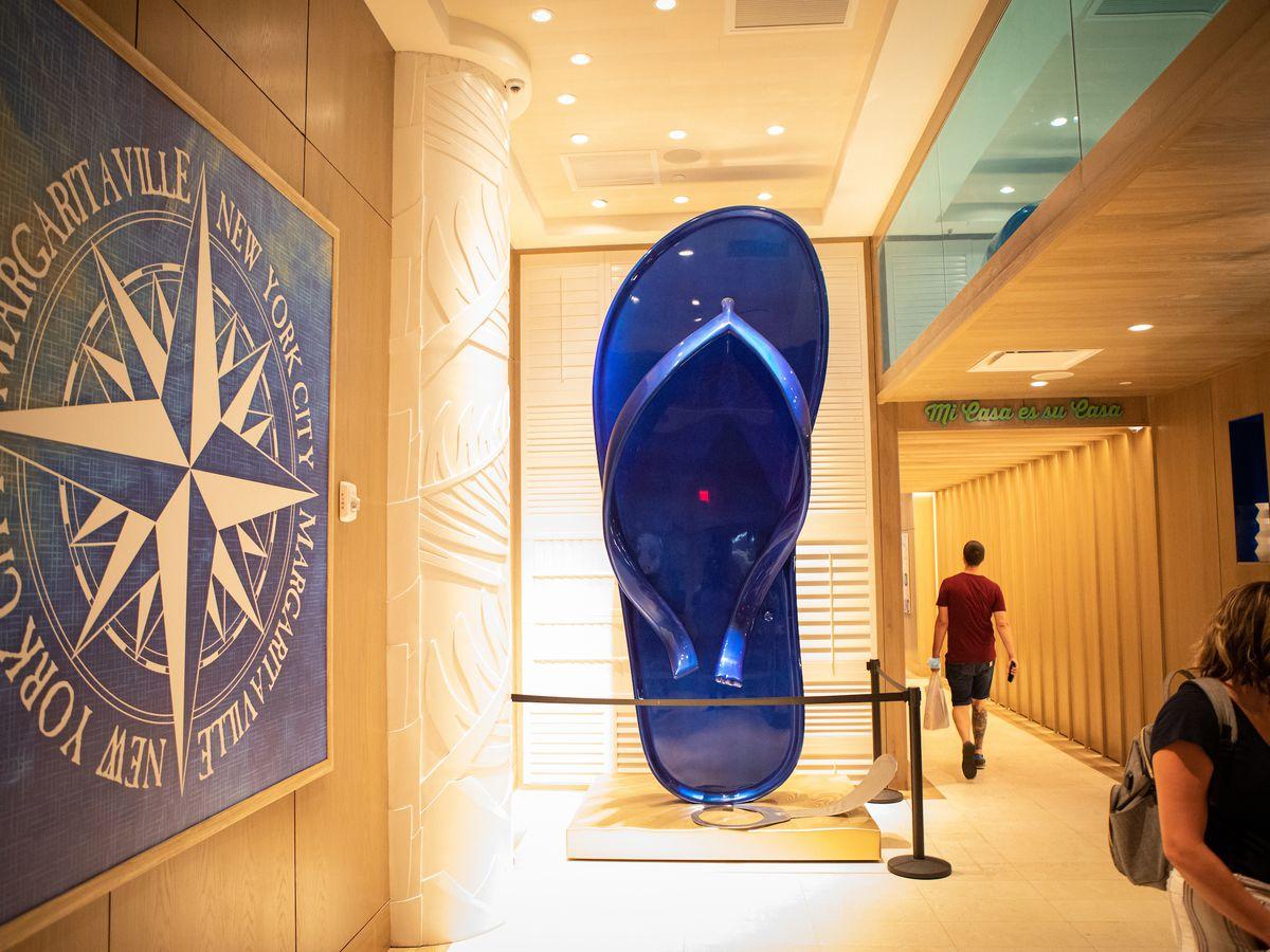 A giant blue flip-flop is encased in glass in a hallway as a man walks past it.