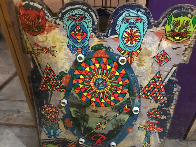 A carnival game with painted monster heads along the top.