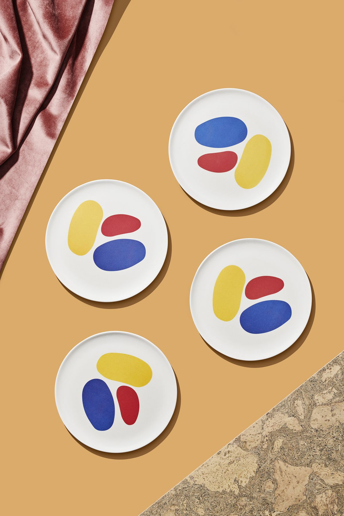 A set of four bamboo salad plates which are white with a multicolor abstract pattern. The plates are part of the 2019 Curbed Holiday Gift Guide. They are sitting on a flat yellow surface and are flanked by various design objects.